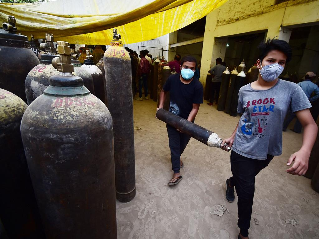 Youths carry a medical oxygen cylinder for a relative sick with COVID-19. Picture: Sanjay Kanojia / AFP