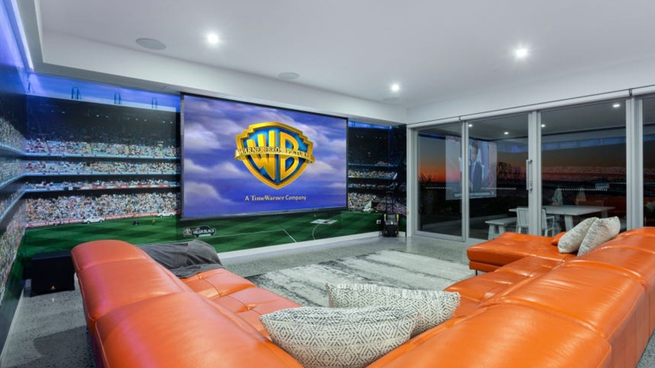 A mural of a roaring MCG crowd in the home theatre creates the atmosphere of a real game.