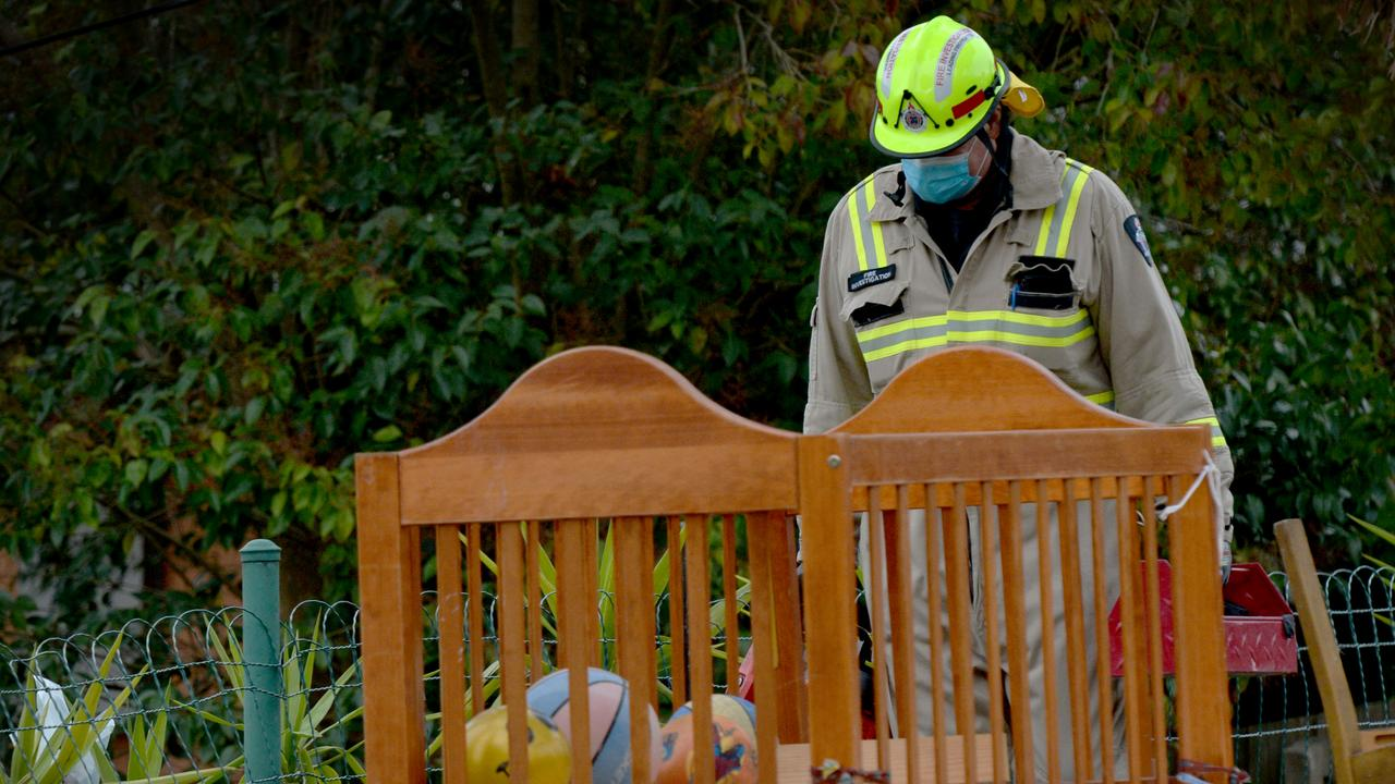 A fire investigator examines a baby's cot at a property in Leonard St, Dandenong where a child died in a blaze overnight. Picture: NCA NewsWire / Andrew Henshaw