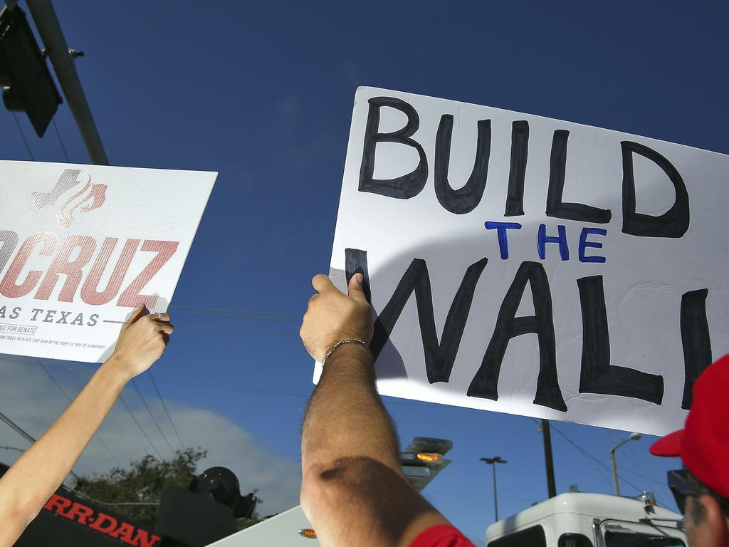 Trump supporters hold up signs during a visit by the US President at McAllen Miller International Airport, Texas on Thursday, Jan. 10, 2019. Picture: AP