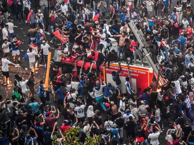 This picture taken from the terrace of the Publicis drugstore on July 15, 2018 shows people standing on a firefighter vehicle after France won the Russia 2018 World Cup final football match between against Croatia, on the Champs-Elysees avenue in Paris. / AFP PHOTO / GERARD JULIEN