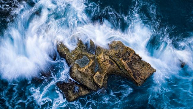 "8/10Best 'Islands' photoRocky outcrop - Taiwan  Photographer's comments: ""An outcrop of rock, battered by the waves, forms its own tiny island just off the coast of Taiwan."" - David Newton"