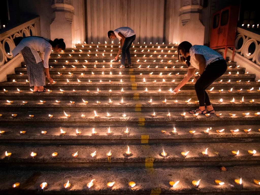 Mourners light candles during a vigil in memory of the bomb blast victims in Colombo. Picture: Jewel Samad