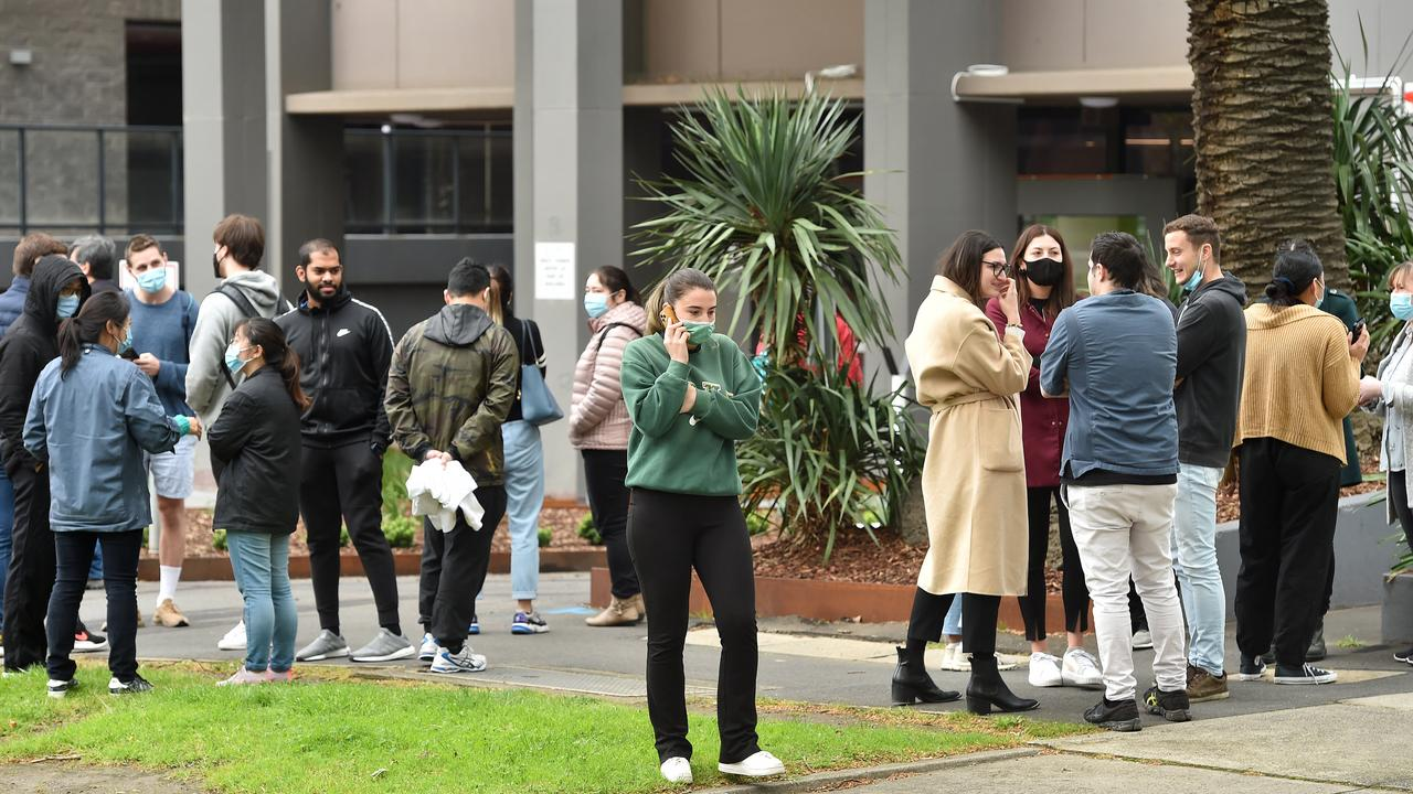 People regroup outside their buildings after the tremor was felt in Melbourne. Picture: Nicki Connolly