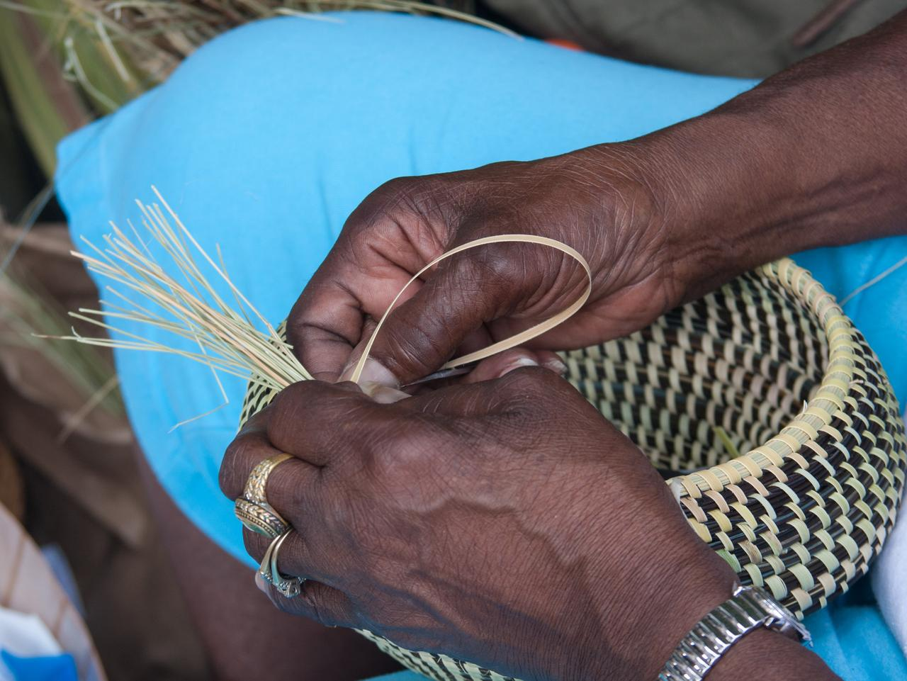 Hands weaving sweetgrass into beautiful baskets