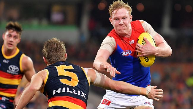 Clayton Oliver of the Demons evades a tackle from Matt Crouch of the Crows.