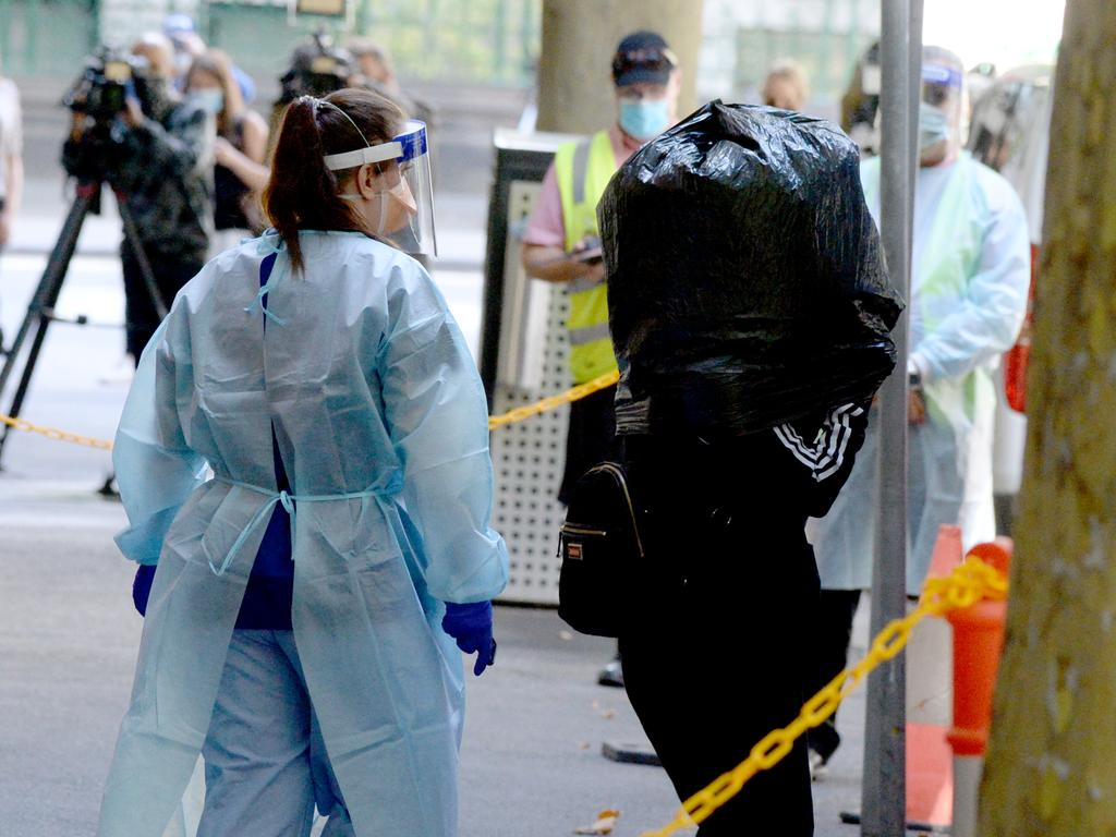 A quarantined international traveller wears a garbage bag on their head as they are evacuated from the Holiday Inn. Picture: NCA NewsWire/Andrew Henshaw