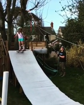 """Denied his family skiing holiday this Easter, a dad in Hertfordshire, England, has gotten creative and built a ski slope, complete with chairlift, in his backyard for his daughters. In a Facebook post, dad Steve Cross said: """"Lockdown project no.2 completed. Seeing as we can't go to the Alps this Easter a spot of skiing at home instead."""" This video shows the girls being hoisted upslope by their father's mechanical chairlift, before zipping down the improvised slope. Credit: Steve Cross via Storyful"""