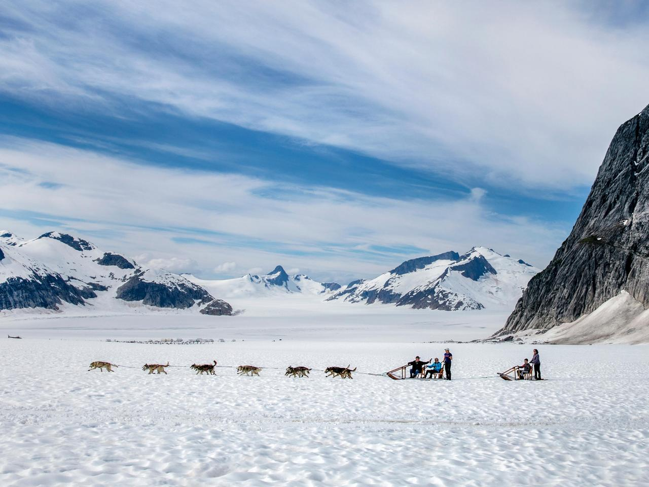 USA, Alaska, Juneau, dogs run below Guardian Mountain on the Juneau Ice Field, Helicopter Dogsled Tour flies you over the Taku Glacier to the HeliMush