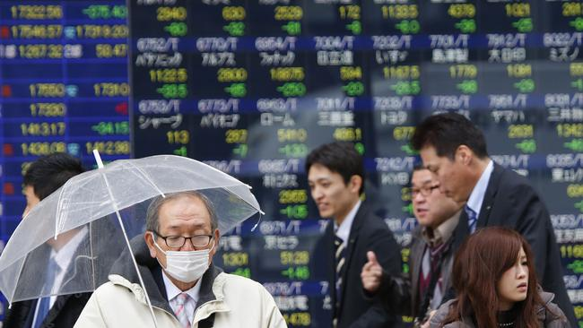 People wait to cross a street in front of an electronic stock indicator of a securities firm in Tokyo. (AP Photo/Shizuo Kambayashi)