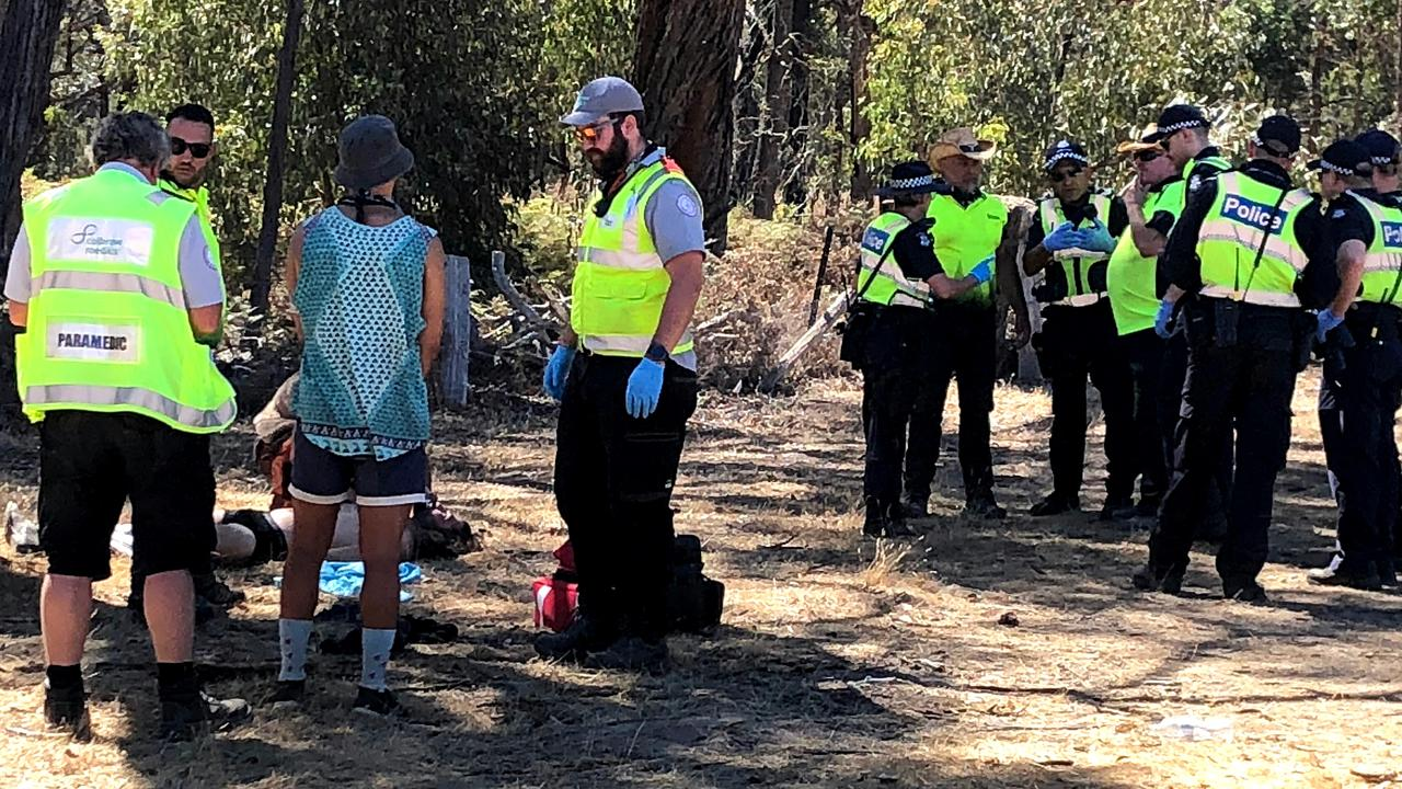 Emergency services attend to a man before he is loaded into an ambulance at the Rainbow Serpent Festival.