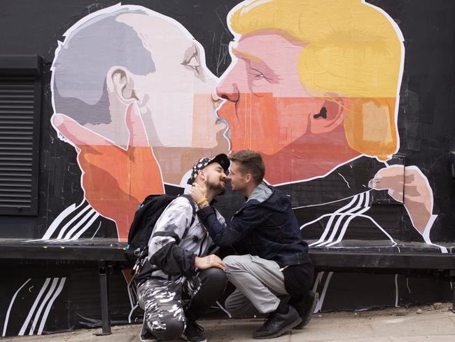 Two men pose in front of a poster showing Donald Trump locking lips with Vladimir Putin in Vilnius, Lithuania. Picture: AP Photo/Liutauras Strimaitis