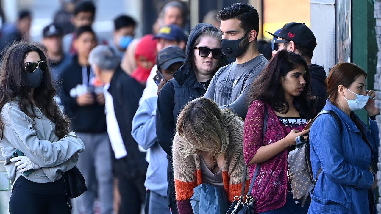 People queuing to enter Centrelink in Melbourne on March 24. The economy will go into a downturn when JobKeeper and JobSeeker are lowered after September. Picture: Quinn Rooney/Getty Images