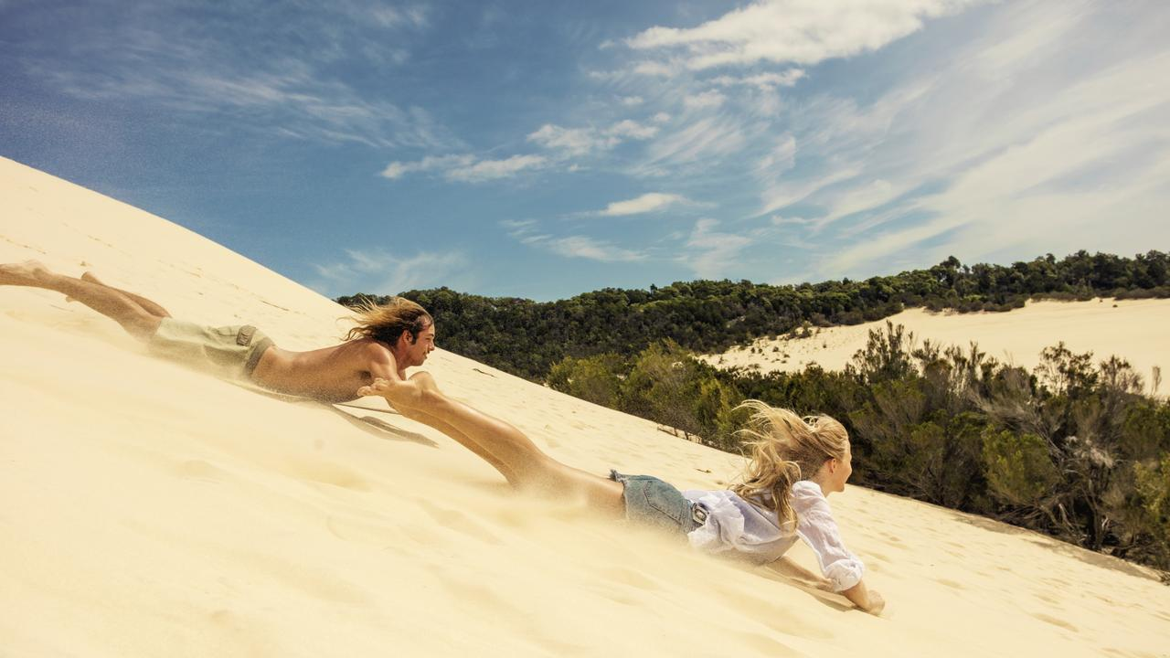 Sandboarding down the sand dunes at Moreton Island.