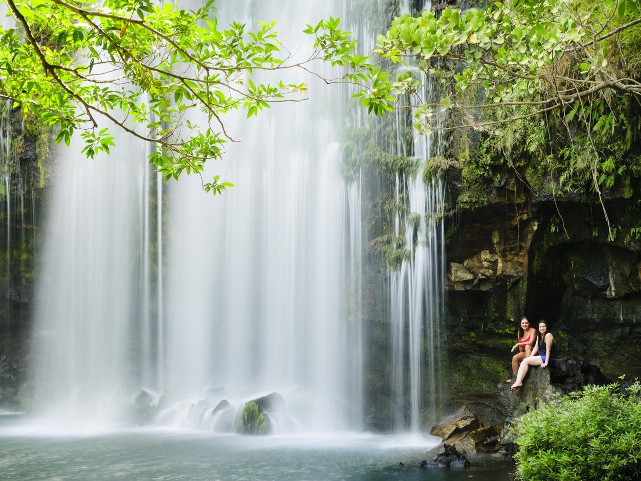 Two women relaxing next to a waterfall. Llanos de Cortes Waterfall in Bagaces, Guanacaste, Costa Rica