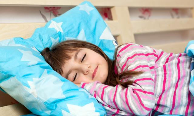 beautiful little girl inHow to remove wee stains from mattress pajamas sleep in bed under a blue blanket