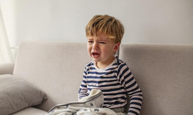 No! Little African baby boy crying while seating on the couch at home. Portrait of crying baby boy. Baby's crying one year old, brunette with brown eyes, hysteria, the crisis of the first year of life.
