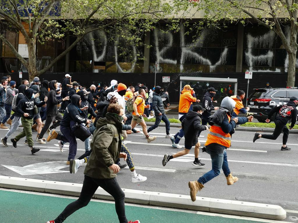 Demonstrators were seen running towards a police car. Picture: STR / AFP