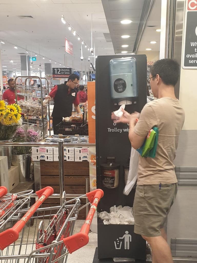 Customers lined up to wipe down their trolleys at a Coles in Sydney yesterday. Picture: Supplied