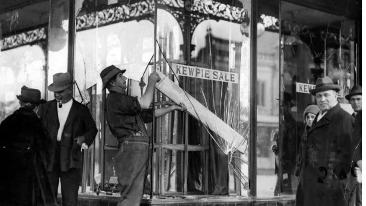 November 6, 1923: Workmen repairing the wrecked windows of Leeming's footwear shop (at the corner of Errol and Victoria St), which was the centre of the previous night's disturbance in North Melbourne.