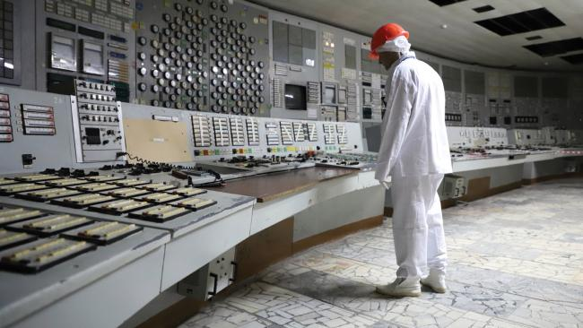 Control Room 2, Chernobyl Nuclear Power Plant. A tourist studies the consoles, decommissioned after a fire in 1991. The controls are no longer operational and occasionally plant employees will allow visitors to push buttons and switches. Picture: Darmon Richter/FUEL Publishing