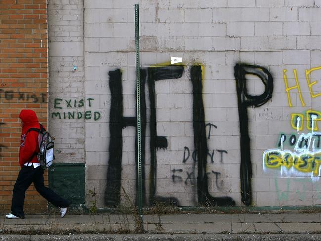 A pedestrian walks by graffiti on a downtown street in Detroit, Michigan, where an estimated one in three live in poverty. Picture: AFP