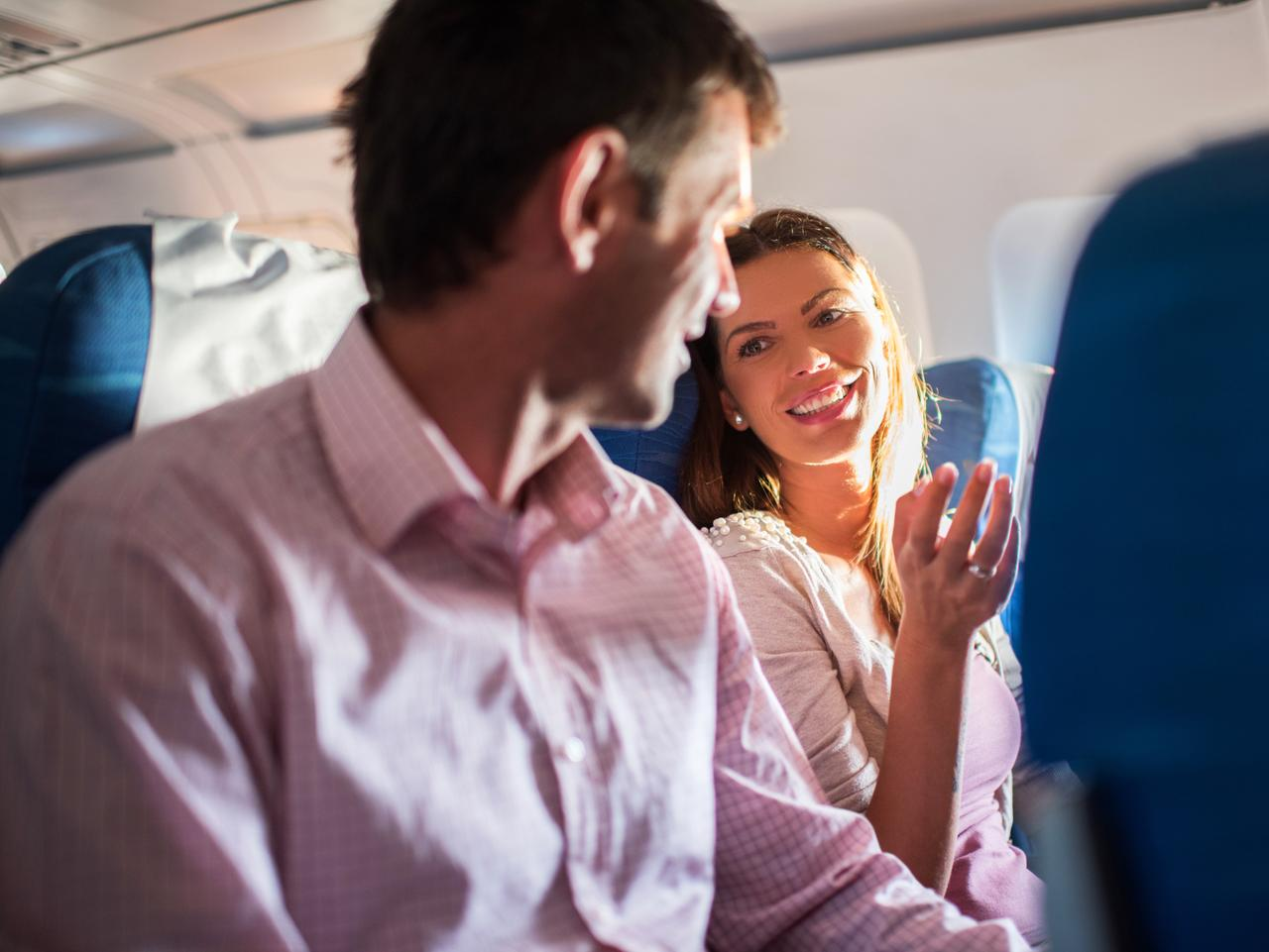 Happy couple sitting in the airplane and communicating. Focus is on woman.