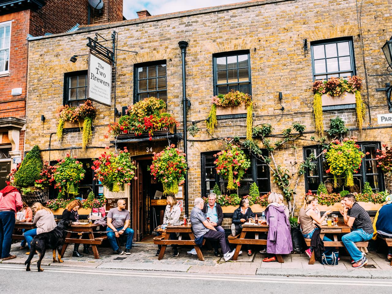 People socialising and sitting outside The Two Brewers public house at Park Street, Windsor, London, England on an overcast autumn day. The pub is located right beside the George IV Gateway at Windsor Castle.