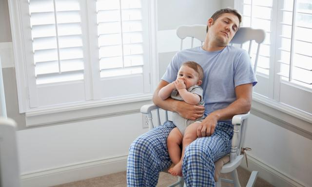 Tired young father (20s) resting in rocking chair with baby (8 months) sitting on lap.