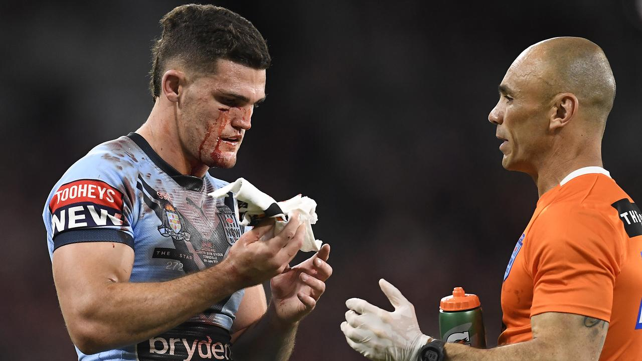 TOWNSVILLE, AUSTRALIA - JUNE 09: Nathan Cleary of the Blues is attended to by a team trainer after a cut to his face during game one of the 2021 State of Origin series between the New South Wales Blues and the Queensland Maroons at Queensland Country Bank Stadium on June 09, 2021 in Townsville, Australia. (Photo by Ian Hitchcock/Getty Images)