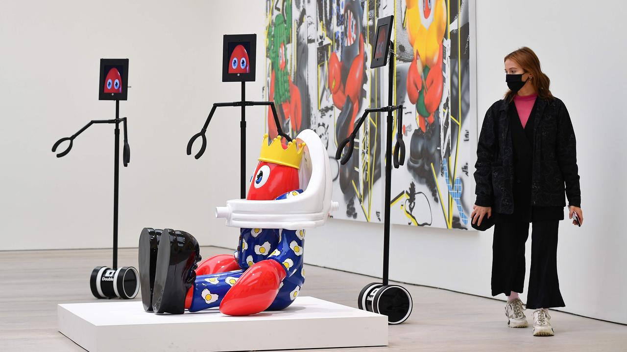 A woman looks at pieces of art alongside remote-view robots that visitors can digitally control to explore the exhibition remotely during a press preview of 'Philip Colbert: Lobsteropolis' at the Saatchi Gallery in London on October 29, 2020. Picture: AFP