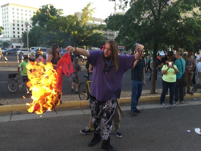 A protester holds a burning T-shirt as hundreds rally against Trump. Picture: Russell Contreras