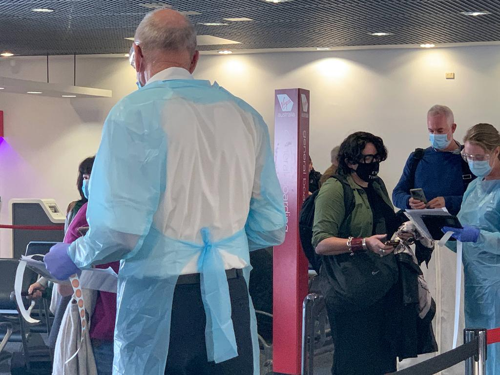 NSW Health workers dressed in Personal Protection Equipment greet passengers travelling from Perth on Virgin flight VA552 at Sydney Airport. Picture: NCA NewsWire/Bianca De Marchi
