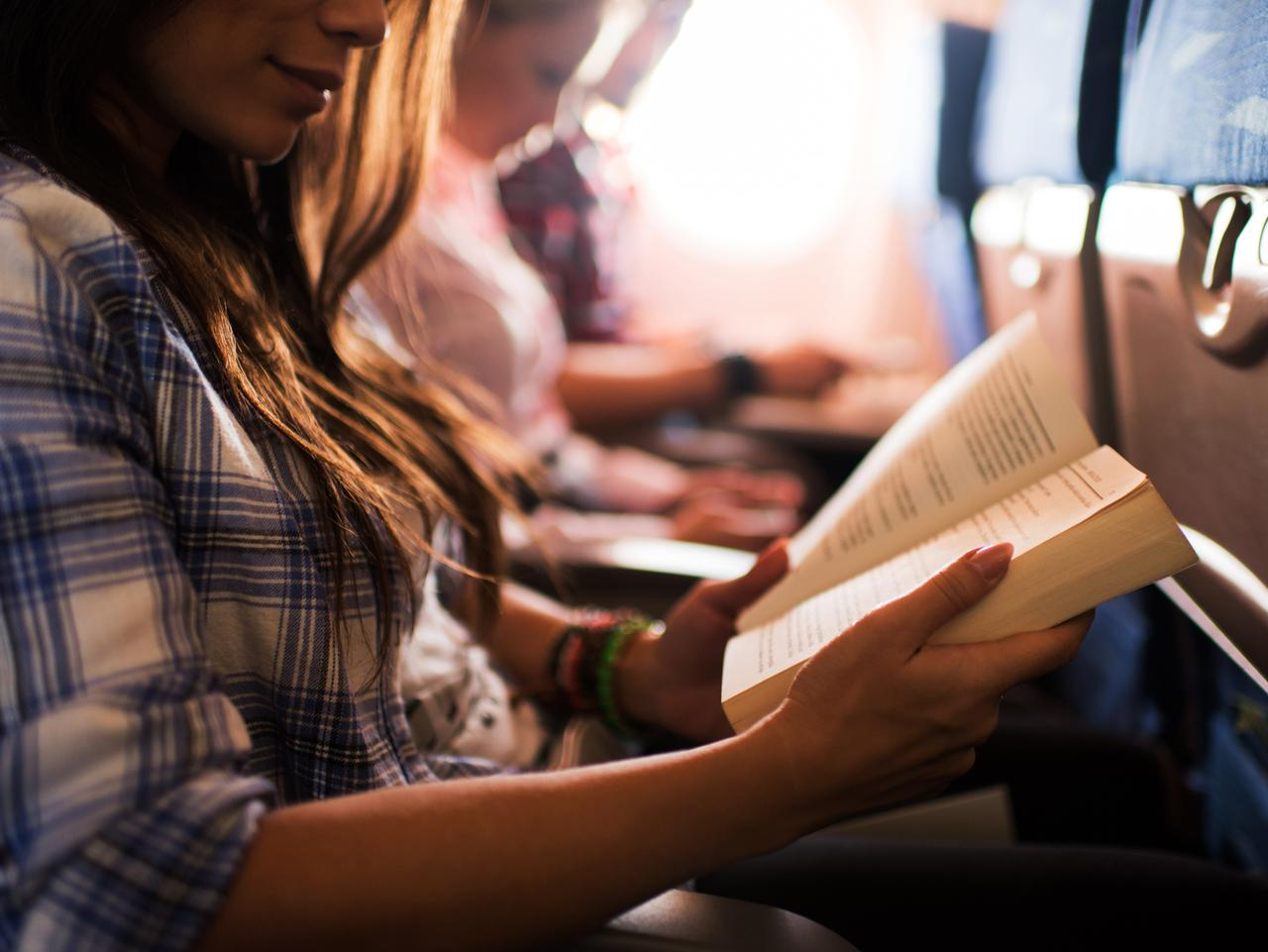 Unrecognizable woman reading a book during her flight.