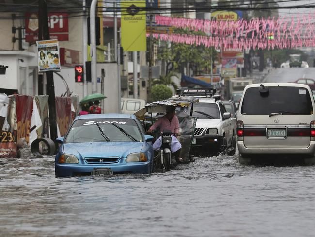 Vehicles navigate a flood-prone area caused by rains from Typhoon Nock-Ten in Quezon City, north of Manila, Philippines.