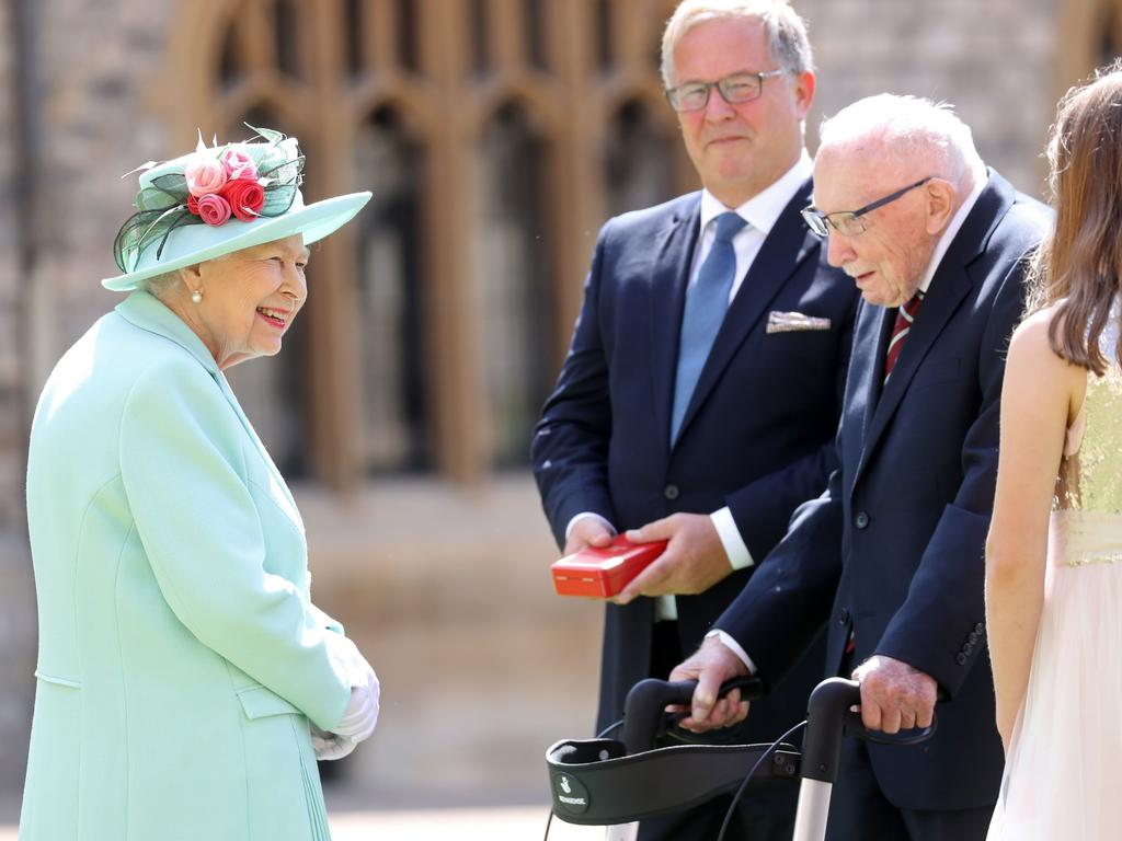 Queen Elizabeth II talks to Captain Tom Moore and his family at his knighthood. Picture: Chris Jackson/AFP