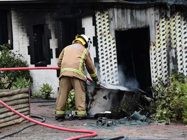 A firefighter works to extinguish the blaze. Picture: Campbell Brodie