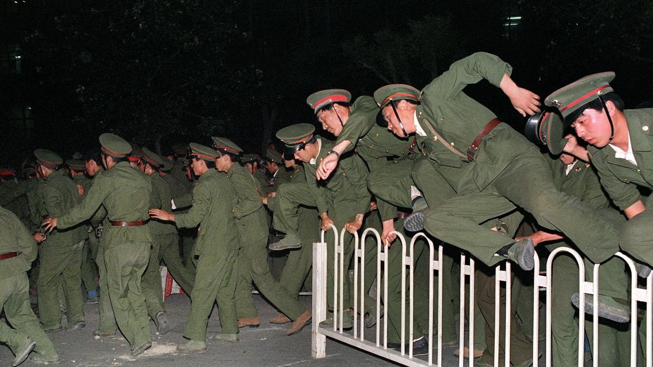 This June 4, 1989 image shows Peoples Liberation Army (PLA) soldiers leaping over a barrier on Tiananmen Square in central Beijing during heavy clashes with students. Picture: Catherine Henriette / AFP