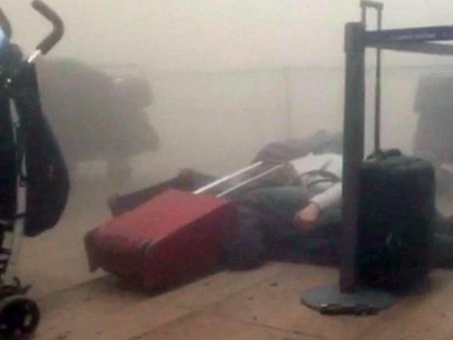 Images from RTL Belgium show travellers lying inside a smoke-filled room after bombs went off. Picture: RTL via AP.