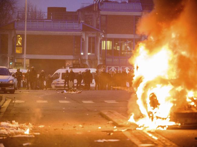 French police officers face protesters as a car burns in Bobigny Picture: Aurelien Morissard