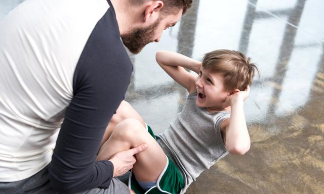 Boy doing sit-ups while trainer holding feet