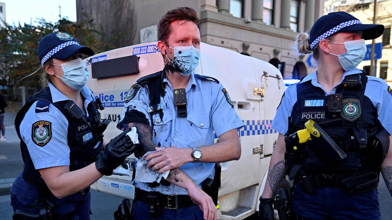 A police officer wipes away the paint thrown by a protester on officers. Picture: AFP