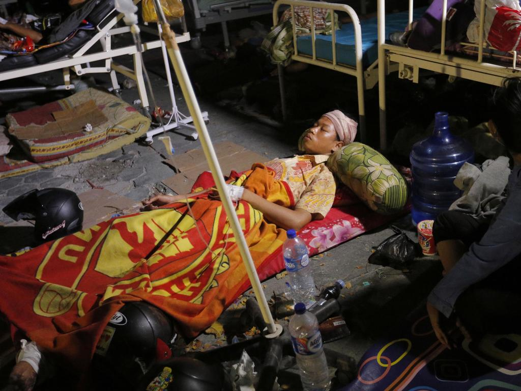 A woman lays while being treated outside an army hospital. Picture: AP