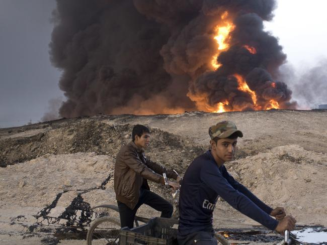 Youths ride bicycles next to a burning oil well in Qayara, about 50 kilometres south of Mosul, Iraq, earlier this month. Picture: AP