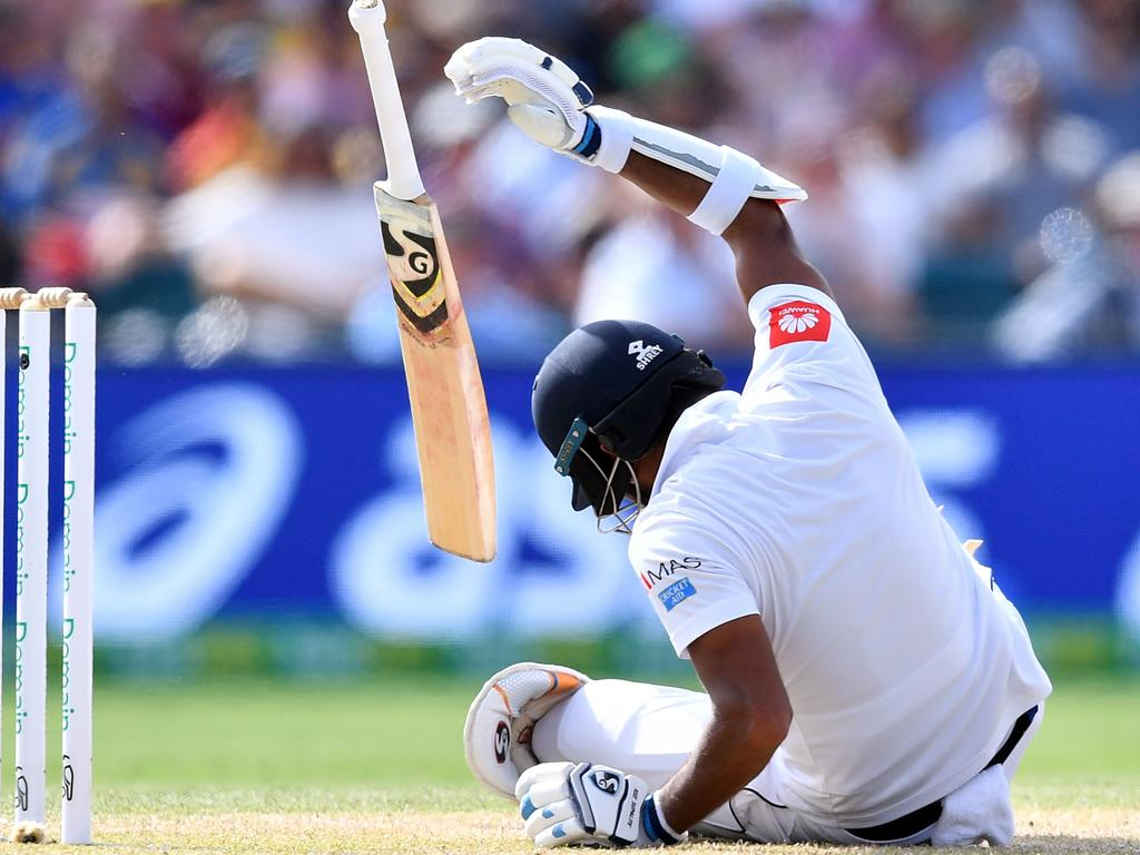 Dimuth Karunaratne falls to the ground after being hit. (Photo by Saeed KHAN / AFP)
