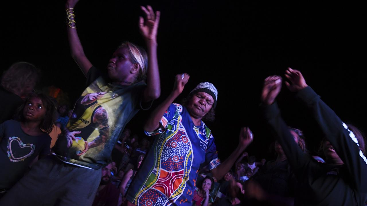 Locals dance during a concert at the official ceremony to celebrate the closure of the climb at Uluru-Kata Tjuta National Park in the Northern Territory. Picture: AAP Image/Lukas Coch.