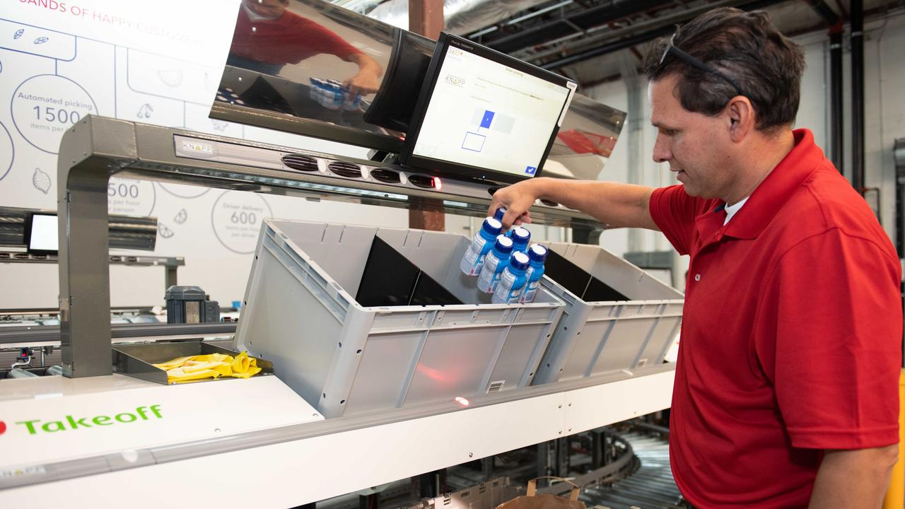 A worker packs groceries at a Takeoff Technologies automated fulfilment centre.