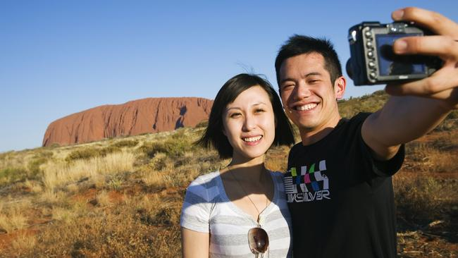 Tourists check out Australia's most famous rock, which is traditionally owned by the Anangu people. Picture: NT Tourism
