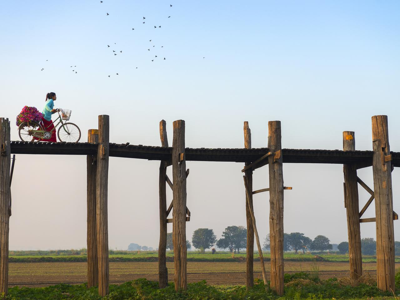 Woman with bicycle crossing U Bein Bridge.