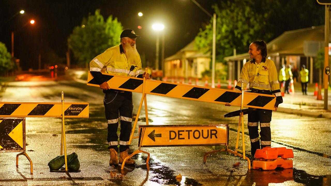 Workers dismantle the roadblock in Albury just before midnight on Sunday. Picture: NCA NewsWire / Simon Dallinger
